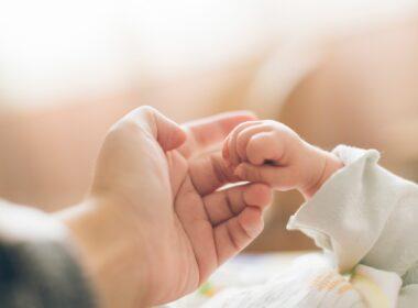 rączka nowonarodzonego dziecka na tle większej dłoni